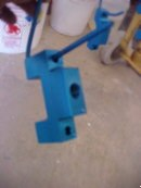 Blue anodized part on anodizing rack after being anodized, dyed, and sealed